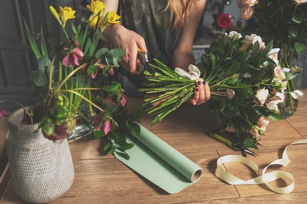 Conceito de loja floral. mulher de florista cria o buquê de flores. lindo buquê de flores mistas. bando fresco bonito.