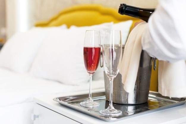 Conceito de lua de mel balde de champanhe perto da cama em um quarto de hotel