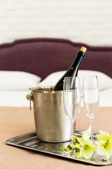 Conceito de lua de mel. balde de champanhe perto da cama em um quarto de hotel