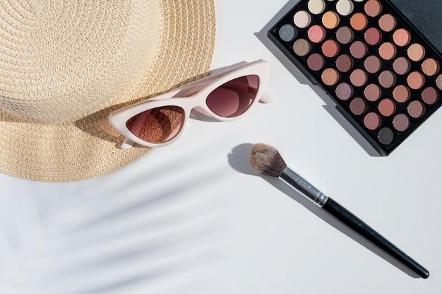 Conceito de mackup e beleza de verão. vista superior do pincel de maquiagem e cosméticos em fundo branco, vista superior