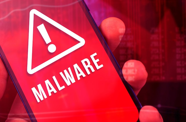 Conceito de malware e crime cibernético, close-up da mão de um hacker anônimo com telefone celular, senha de hack, conta bancária e dados pessoais