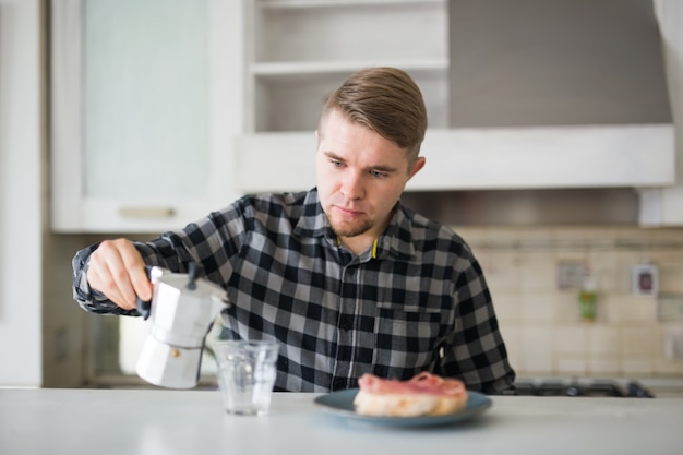 Conceito de manhã, bebida e pessoas - retrato de um homem bonito servindo café em uma caneca de café no