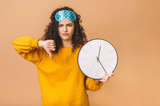 Conceito de manhã. jovem encaracolada bonita posando sobre fundo bege com relógio e máscara de dormir.