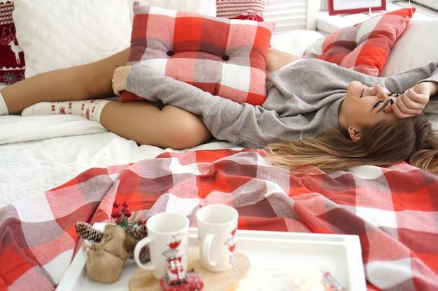 Conceito de manhã, lazer, natal, inverno e pessoas jovem feliz na cama