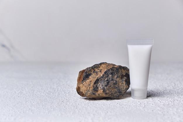 Conceito de maquete de verão para apresentação de produto tubo de garrafa cosmética e plataforma de pedra em fundo branco texturizado