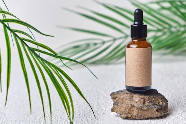 Conceito de maquete de verão para frasco cosmético de apresentação de produto na plataforma de pedra. frasco conta-gotas de vidro marrom com rótulo em branco sobre fundo branco com folhas verdes de palmeira