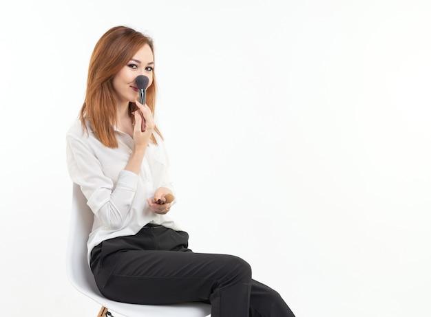 Conceito de maquiador, beleza e cosméticos - engraçado maquiador feminino coreano com pincéis de maquiagem em fundo branco