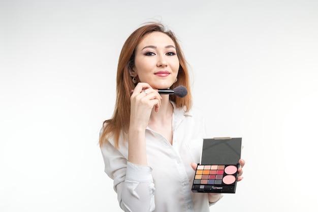 Conceito de maquiador, beleza e cosméticos - maquiadora coreana com pincéis de maquiagem e paleta de sombras na parede branca