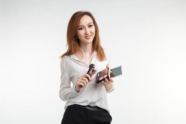 Conceito de maquiador, beleza e cosméticos - maquiadora coreana com pincéis de maquiagem e paleta de sombras no fundo branco
