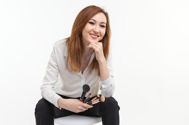 Conceito de maquiador, beleza e cosméticos - maquiadora coreana com pincéis de maquiagem em fundo branco