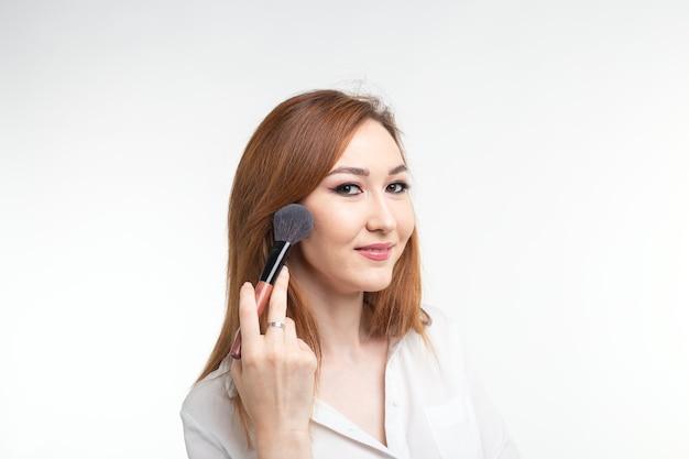 Conceito de maquiador, beleza e cosméticos - maquiadora coreana com pincéis de maquiagem na parede branca