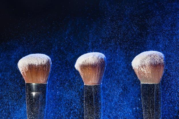 Conceito de maquiagem, beleza e pó mineral - pincele com pó azul sobre fundo preto