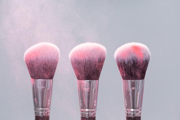 Conceito de maquiagem, beleza e pó mineral - pincele com pó rosa sobre fundo claro.