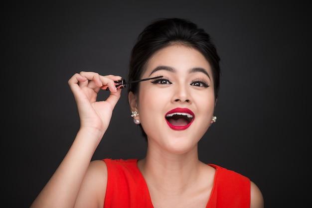 Conceito de maquiagem e cosméticos. mulher asiática fazendo sua maquiagem cílios rímel preto.