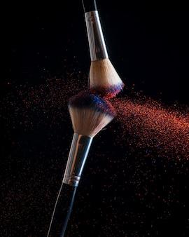 Conceito de maquiagem. pare a visualização de ação de dois pincéis de maquiagem aplicando o pó vermelho e dourado correspondente