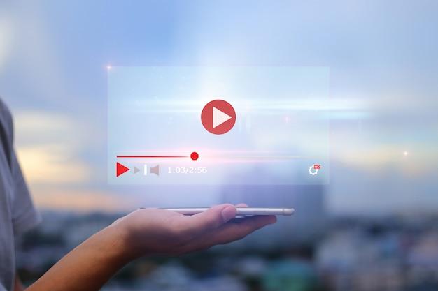 Conceito de marketing de streaming on-line de conteúdo de vídeo ao vivo. mãos segurando o telefone móvel na cidade urbana turva