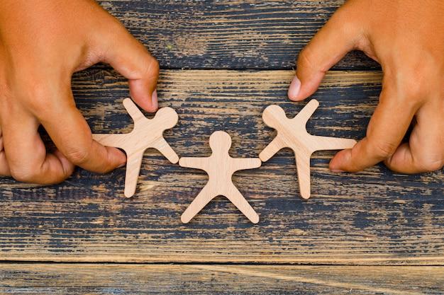 Conceito de marketing no fundo de madeira plana leigos. mãos tocando figuras de madeira.