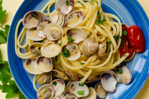 Conceito de massa de marisco italiano tradicional. macarrão com amêijoas ou prateleira, tomate e ervas.