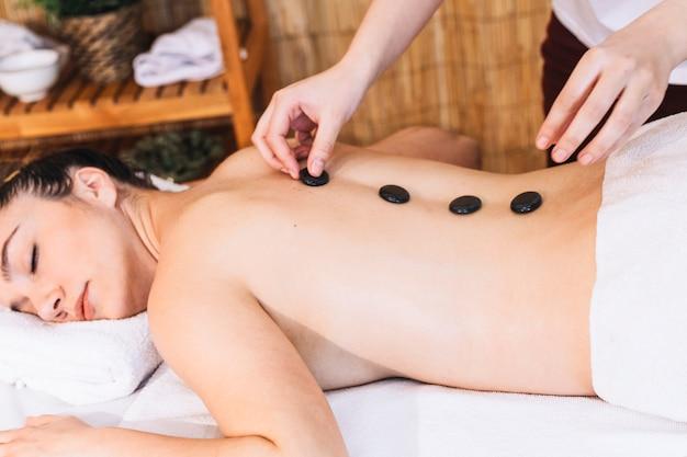 Conceito de massagem com pedras nas costas da mulher