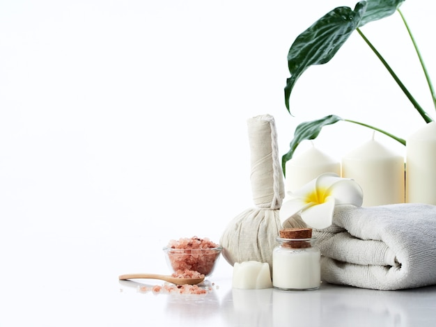 Conceito de massagem spa, bola compressa de ervas, creme, sabonete de flores, vela perfumada e sal rosa do himalaia, isolado