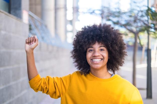 Conceito de matéria de vidas negras. uma séria jovem africana ou americana com o braço para cima com a mão próxima, olhando para a câmera.