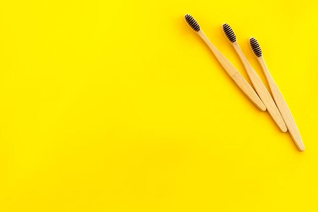 Conceito de materiais ecológicos com escova de dente de bambu em amarelo