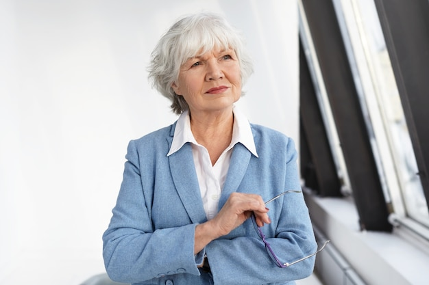 Conceito de maturidade, envelhecimento e emprego. atraente experiente empresária madura vestida com um elegante casaco azul sobre uma camisa branca, pensando em seu escritório, segurando os óculos e sorrindo