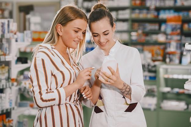Conceito de medicina, farmacêutica, saúde e pessoas. farmacêutica feminina aconselha o comprador.
