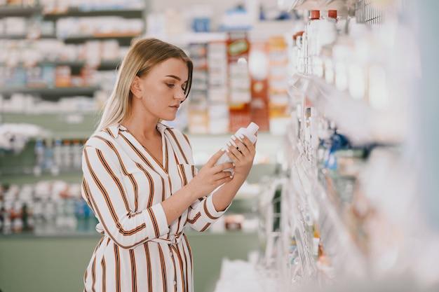 Conceito de medicina, farmacêutica, saúde e pessoas. mulher tomando medicamentos da prateleira. comprador.