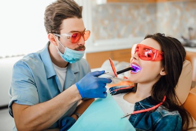 Conceito de medicina, odontologia e saúde, dentista usando lâmpada uv de cura dentária nos dentes do paciente.