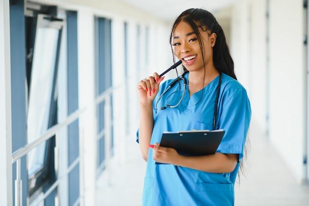 Conceito de medicina, profissão e saúde - médica afro-americana sorridente e feliz com estetoscópio sobre o fundo do hospital