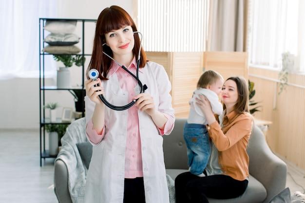 Conceito de medicina, saúde, pediatria e pessoas - médico feminino atraente na frente da mulher com bebê, visita do médico em casa