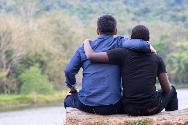 Conceito de melhores amigos, homem africano e homem asiático abraçando com feliz