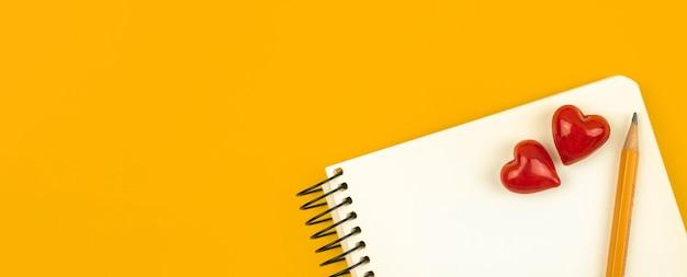 Conceito de mensagem ou carta de casal de amor na escola, banner com bloco de notas branco, dois corações vermelhos e lápis, espaço de cópia, mesa amarela, foto de vista superior