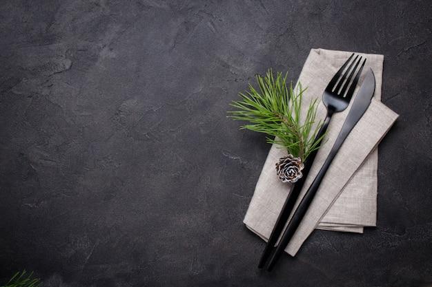 Conceito de menu de natal. postura plana com decorações de natal e pinhas, garfo escuro e faca com guardanapo. copie o espaço