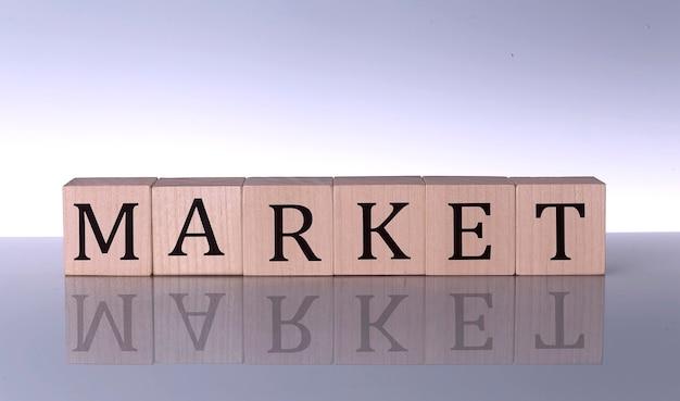Conceito de mercado, bloco de palavras de madeira no fundo cinza