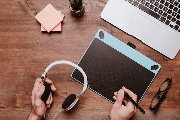 Conceito de mesa de madeira com desenho de mãos no tablet de design e auscultadores