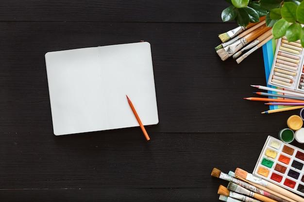 Conceito de mesa de trabalho de arte criativa, pincéis de caderno em branco e paintbox