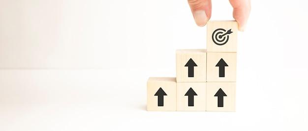 Conceito de meta de negócios de realização, empresário segurando e empilhando blocos de cubos de madeira que imprimem