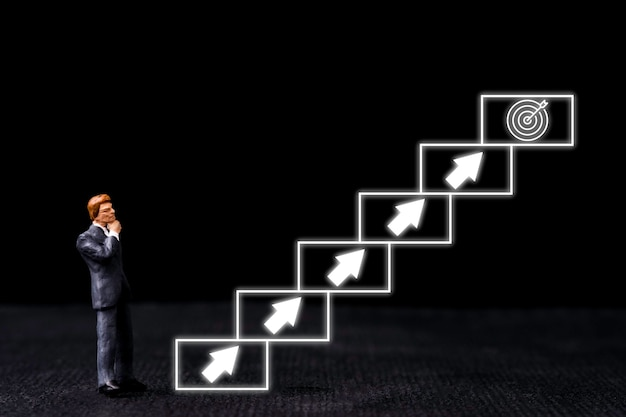 Conceito de meta de negócios de realização, miniatura de empresário em pé ao lado da escada virtual