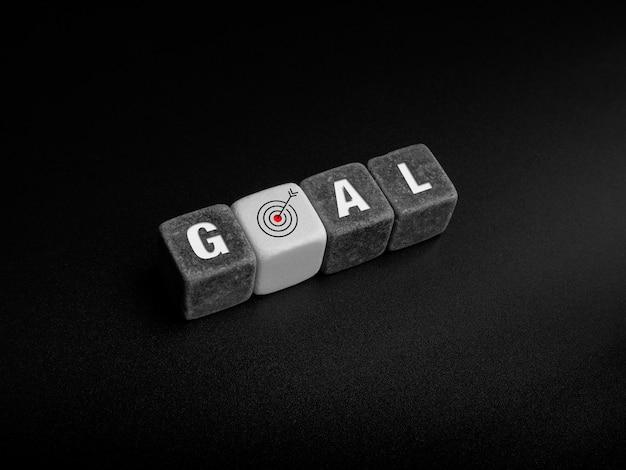 Conceito de metas. ícone de objetivo, palavra e alvo assinam em blocos de cubo preto e branco e seta organizando em fundo escuro, vista superior.