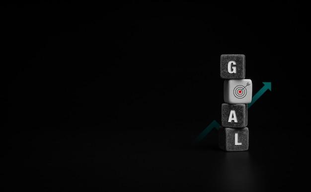 Conceito de metas. objetivo, palavra e ícone de destino assinam em preto e branco empilhando blocos de cubo com seta para cima, gráfico de gráfico de crescimento em fundo escuro com espaço de cópia.
