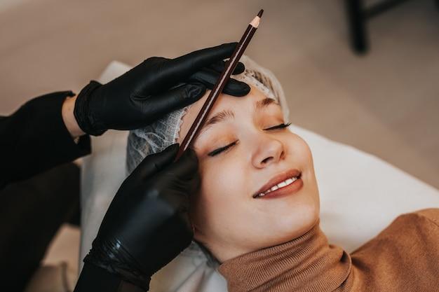 Conceito de microblading de sobrancelhas. cosmetologista preparando jovem para o procedimento de maquiagem definitiva de sobrancelha.