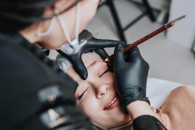 Conceito de microblading de sobrancelhas, procedimento de maquiagem definitiva de sobrancelha. a especialista em beleza está usando escudo e máscara protetora devido à pandemia do coronavírus.