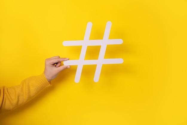 Conceito de mídia social, close de uma mão humana segurando e mostrando uma grande placa de hashtag branca