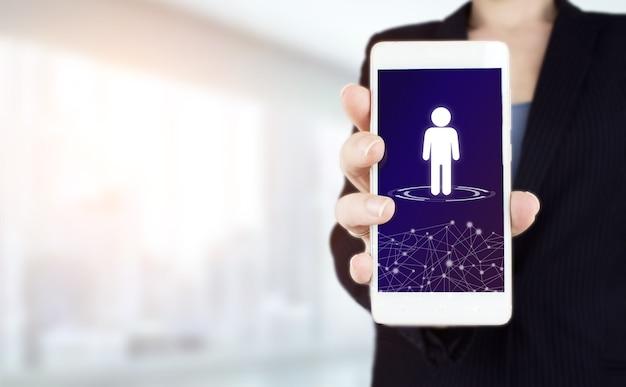 Conceito de mídia social. rede de comunicação. mão segure smartphone branco com holograma digital humano, líder cadastre-se na luz de fundo desfocado. perfil do cliente em um aplicativo móvel.