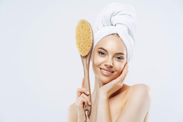 Conceito de mimos de beleza e higiene. mulher sorridente terna tem uma pele saudável segura uma escova de massagem macia de madeira