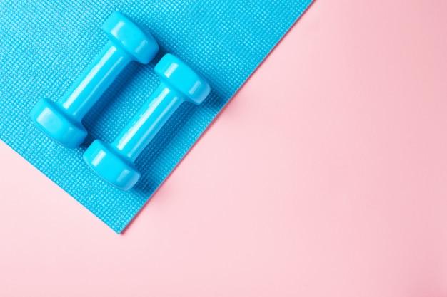 Conceito de minimalismo de fitnes. halteres e sutiã esportivo em um fundo azul e rosa
