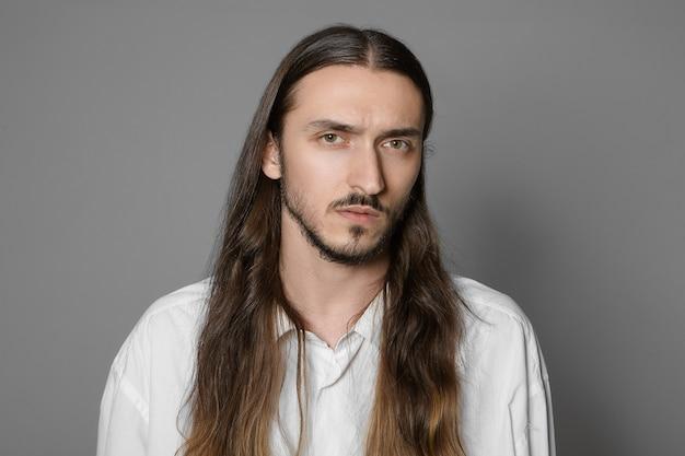 Conceito de moda, beleza e estilo. cabeça e ombros de um homem sério de barba com pele pálida e rosto cabeludo com longos cabelos castanhos soltos