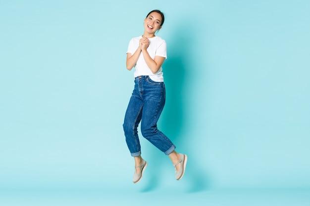 Conceito de moda, beleza e estilo de vida. feliz e sonhadora, excitada garota asiática em roupa casual, pulando de felicidade e alegria, batendo palmas com entusiasmo, em pé sobre a parede azul claro